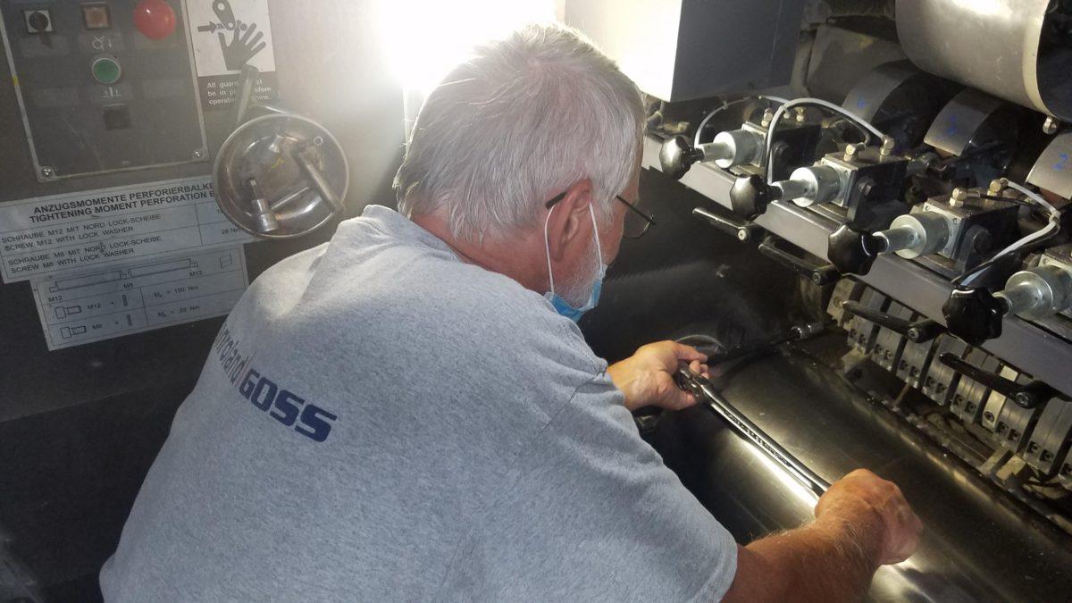 engineer working on printing press